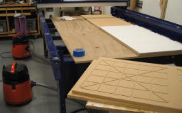 Gluing the MDF platen down in four pieces - the first piece is done, the second is being glued (using a melamine cover to block the airflow), and the third piece, shown upside down, is ready to go.