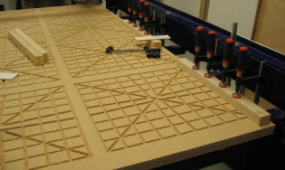 The vacuum grooves are cut and hardwood edging is being glued to the underside of the perimeter.