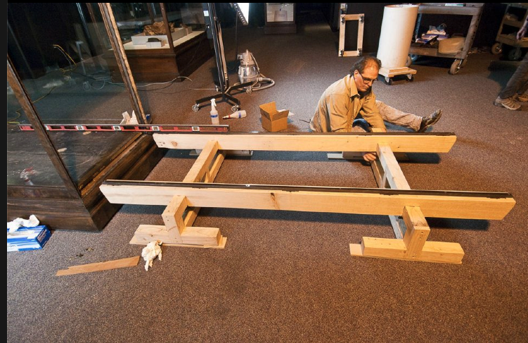 Setting up and leveling the rails which support the case deck prior to installation.