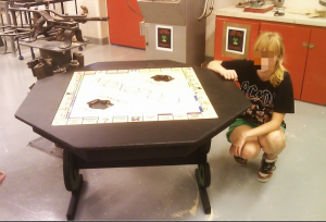 Student shows off Monopoly game and table that she worked on