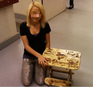 Student with her small table project. Faces blurred for privacy.