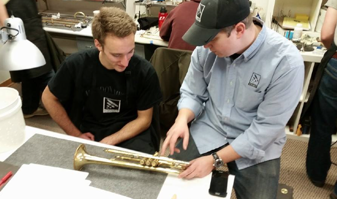 Students learning to repair a trumpet