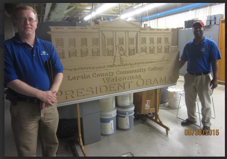 Robert Koonce and Allen Smith,at LCCC's Fab Lab, displaying plaque they designed and cut on ShopBot to welcome President Obama.