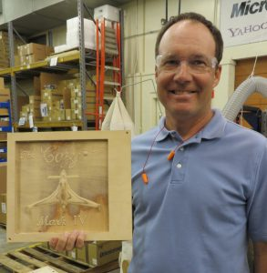 man holding wooden CNC carved bas relief model