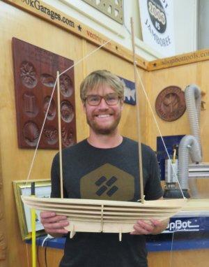 man holding wooden boat model