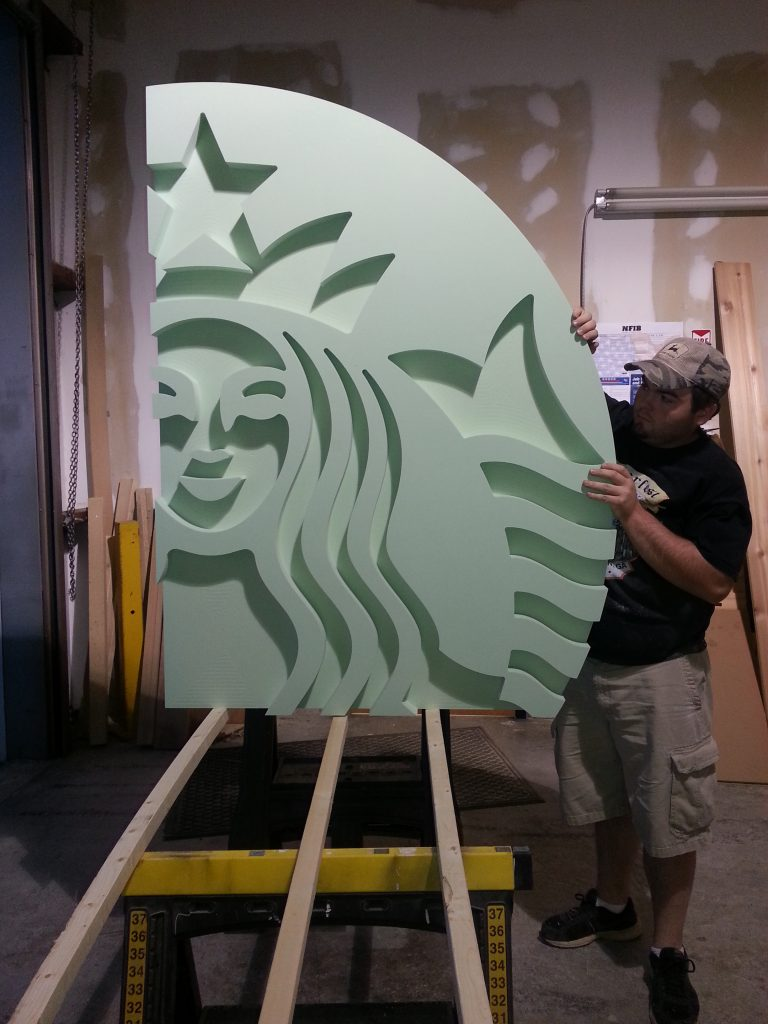 a man holding up the fully cut starbucks wall installation